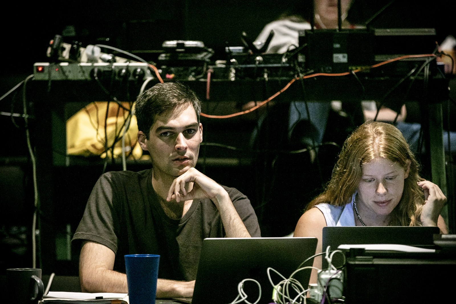 Elias Jamieson Brown, a young white man, sits pensively behind his laptop in the seating banks of the SBW Stables Theatre. Next to him, designer Emma White, a young white woman with red hair, looks at her own laptop. Behind him, a desk full of cords and theatre equipment sits on a raised seating bank.